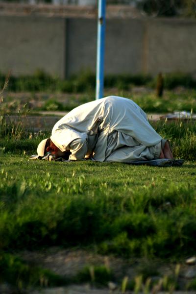"""칸다하르 시 외곽 한 잔디밭에서 무슬림 남성이 저녁 기도를 드리고 있다. 하루 다섯 번 기도를 드리며 쿠란의 가르침을 충실히 따르는 이런 모습은 아프간 전역에서 어렵지 않게 볼 수 있다. 그러나 """"여성을 동등한 인격체로 존중하라""""는 쿠란의 또 다른 가르침은 이슬람 근본주의의 영향력이 큰 아프간 부족 사회에서 찾아보기 힘들다. 여성의 활동을 제약하고 매매하는 부족 관습이 '이슬람'과 '전통'의 이름으로 정당화되기 때문이다. 그 근본주의를 키워 온 게 바로 80년대 '반공' '반소' 전선에 돈과 무기를 퍼부었던 미 제국주의다.(Photo by Lee Yu Kyung)"""