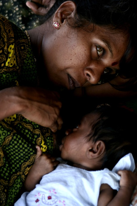 "A Tamil woman nurses her one year old baby, who was borned in IDPs camp in Batticaloa, where a few more IDPs camp was running as of visiting time in the mid of 2009. Hundreds of IDPs in this camp were from upper part of Eastern province, where the Sri Lankan army had retaken the territory from Tamil Tigers, the rebel group in 2007. However, IDPs were not alllow to return their home for years. The earlier ""liberated"" east has remained then abductions rampaged and violence committed by paramilitary forces and the armed forces. Ramnants of LTTE were also said to be active as of the mid of 2009. (Photo @ Yu K. Lee)"