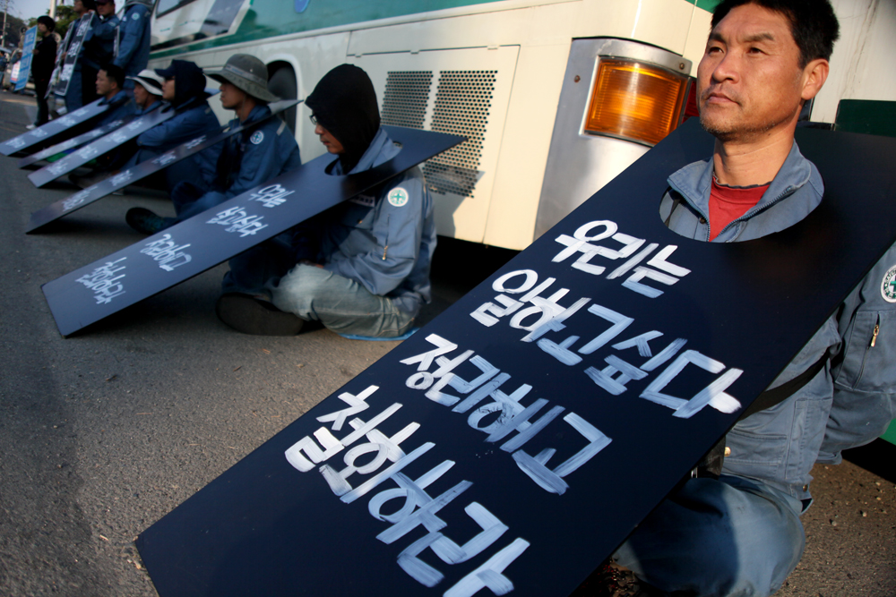 """We want to back to our working place. Withdraw the lay off"" reads the banner of a worker at morning campaign, which                  HHIC laid off workers organize in front of the main gate of the company every morning. (Photo @ Lee Yu Kyung)"