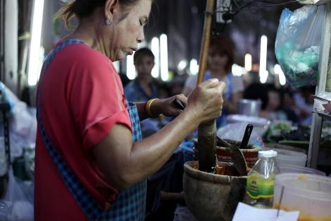 방콕 거리식당 주인이 쏭땀 (파파야 살라드)을 만들고 있다. 매콤하고 강한 맛에 입맛 돋구는 인기음식이지만 미원 MSG가 듬뿍 들어간다. 싸고 맛있는 거리음식은 간헐적 외식으로 별미효과를 볼 수 있지만, 끼니로 이어간다면 건강한 식습관 유지에 지장을 줄 수 있다. (Photo © Lee Yu Kyung)