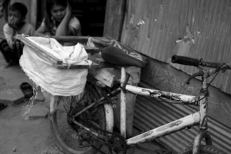 Chan Chao Loy (or 'Loy'), a 12 year old waster picker in Cambodia, has a bicycle with broken brake, which he drives every day during waste picking work starting from 4 or 5 am to last 3-4 hours. (Photo © Lee Yu Kyung 2013)
