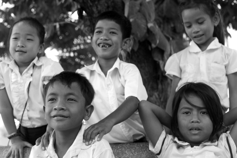 Chan Chao Loy (or 'Loy', front left) and his friends sitting in a playground of the school. Loy, a 12 year old waste picker, is attending 4th grade. Some of his class mates also do waste picking for a living. Loy's daily income, which amounts to 1000 riels (0.25 USD) on average, has been contributing family's living. (Photo © Lee Yu Kyung 2013