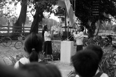To finalize school hours, Chan Chao Loy (or 'Loy', right), a 12 year old waste picker and his class mate are taking down a national flag in school's playground. (Photo © Lee Yu Kyung 2013)