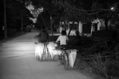 Chan Chao Loy (or 'Loy'), a 12 year old waste picker, is driving his brake-broken bicycle for a work with his friend at dawn. (Photo © Lee Yu Kyung 2013)