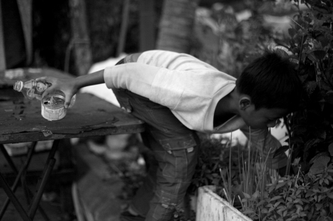 A 12 year old Chan Chao Loy (or 'Loy'), one of thousands waste picking children in Cambodia, is searching for recycling materials in the early morning while he works. He never skipped a work for the past two years. (Photo © Lee Yu Kyung 2013)