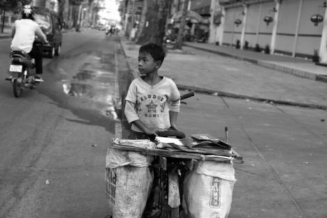 Chan Chor Loy (or 'Loy'), a 12 year old waster picker in Cambodia, is looking at opposite side of the road as he found a huge rubbish bin, in which he must have expected lots of recycling materials. (Photo © Lee Yu Kyung 2013)