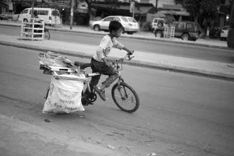 Having added more recycling stuffs, Chan Chor Loy (or 'Loy'), a 12 year old waster picker in Cambodia, is pushing his brake-broken bikes. (Photo © Lee Yu Kyung 2013)