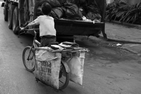 Chan Chao Loy (or 'Loy'), a 12 year old, is pushing hard his brake-broken bicycle seemingly to attempt to pass ahead garbage truck. He is one of thousands waste picking children in Cambodia. His both parents are HIV positive.(Photo © Lee Yu Kyung 2013)
