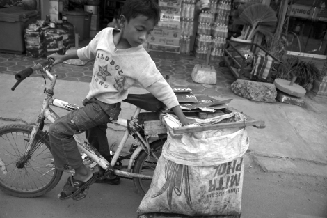 Chan Chor Loy (or 'Loy'), a 12 year old waster picker in Cambodia, is reorganizing his collected recycling materials before moving ahead. (Photo © Lee Yu Kyung 2013)
