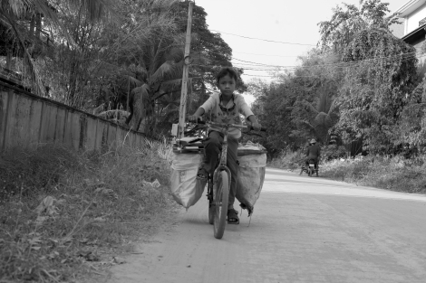 Chan Chor Loy (or 'Loy') is nearing his neighborhood from working field, in which he has picked plastics, cans, papers and other recycling materials. Loy is one of thousands waste picking children in Cambodia. (Photo © Lee Yu Kyung 2013)
