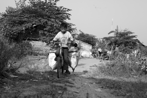 Chan Chor Loy (or 'Loy') is arriving his neighborhood from working field, in which he has picked plastics, cans, papers and other recycling materials. Loy is one of thousands waste picking children in Cambodia. (Photo © Lee Yu Kyung 2013)