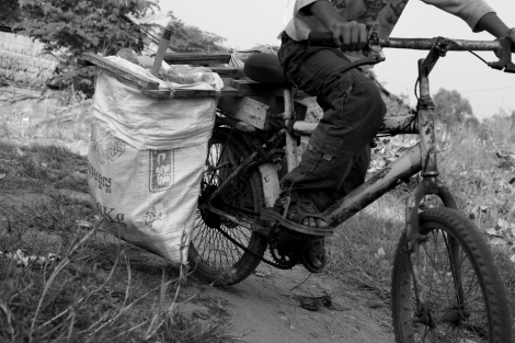 Chan Chor Loy (or 'Loy') is nearing his home from working field, in which he has picked plastics, cans, papers and other recycling materials. Loy is one of thousands waste picking children in Cambodia. (Photo © Lee Yu Kyung 2013)