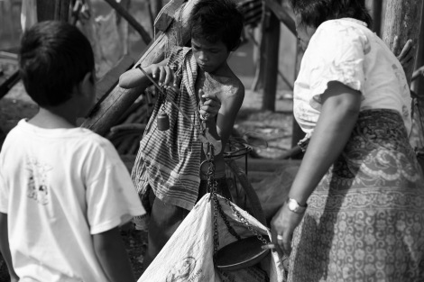 Waste pickers in Phnom Khnom, one of many villages near Tonle Sap Lake in Siem Reap in Cambodia, are scaling their collected recycling materials. Woman (right) buys recycling materials from children who all are waste pickers. (Photo © Lee Yu Kyung 2013)