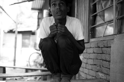 Mohamad Rafik, ein 17-jähriger Rohingya aus dem Arakan-Staat in Myanmar, demonstriert die Position, in der er und seine Leidensgefährten während der Flucht über See tagelang verharren mussten. (Foto: Lee Yu Kyung)