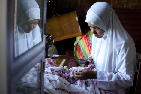 메이크틸라의 한 민가에서 무슬림 여성이 옷을 수선하고 있다. 지난 3월 학살 사건 이후 수천 명의 무슬림들은 생활 기반을 잃고 막막한 삶을 이어가고 있다. (Photo © Lee Yu Kyung 2013)