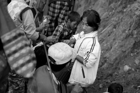 The fleeing Kachin IDPs bumping along a cliffside dirt road in the back of a rickety truck. (Photo © Lee Yu Kyung 2013)