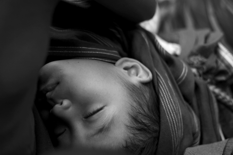 An IDP child on a rickety truck sleeping while traveling on cliffside dirt road (Photo © Lee Yu Kyung 2013)