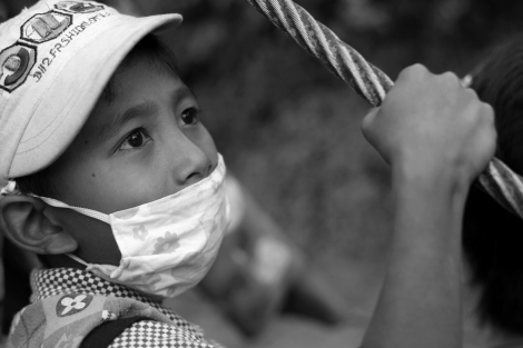 An IDP child firmly holds rope which are attached to the truck for safety purpose as the truck doesn't have enclosing walls. (Photo © Lee Yu Kyung 2013)