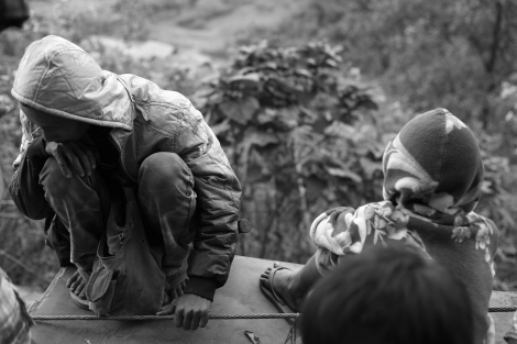 An IDP man and a child sitting  on the truck which is transporting them to safe place through the cliffy bumping road in Mansi Township. (Photo © Lee Yu Kyung 2013)