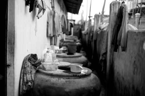 프놈펜 남서쪽 카나디아 공단 부근 월세 25달러짜리 거처 벽면. 화장실이나 세면시설은 따로 없으며 벽을 끼고 늘어선 큰 항아리에 물을 담아 요리, 세면 등을 해결한다. (Photo © Lee Yu Kyung 2013)