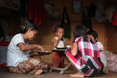 라이자 부근 한 피난민 캠프에서 할머니와  손주들이 식사 중이다.  벽에  걸린 사진 속  병사는 전쟁 중  전사한 아이들의 아버지이다.  지난  2년여 동안 전쟁으로 카친 주  피난민  수는10만명을 웃돌고  있다. 이중  7만5천명  가량이 유엔과  국제엔지오의  구호를  제대로  받지 못하는 반군영토에  머물고  있다. (Photo © Lee Yu Kyung 2013)