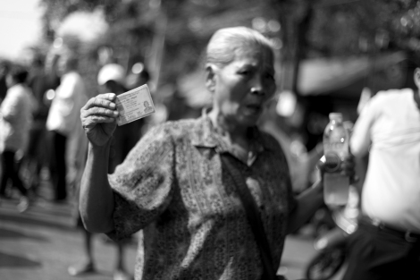 An elderly show her ID card in a frustration as she could not vote thanks to anti-government protesters (or PDRC) in Din Daeng, Bangkok.