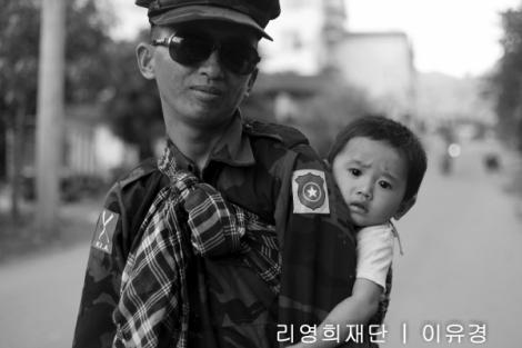 카친 병사가 아이를 보고 있다. 17년 휴전이 깨진 이래 재개된 전쟁으로 지난 2년여간 카친반군의 젊은 병사들은 교전에 집중 노출되고 있다. (Photo © Lee Yu Kyung)