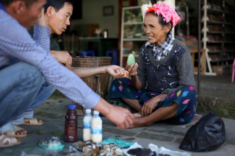Lisu woman is trying to sell jade to Chinese men in Laiza. The one she's holding up costs 1,000 CNY ($160 USD). Jade is one of affluent natural resources in Kachin state, which are said to be partly factor of the ongoing conflict.  (Photo © Lee Yu Kyung)