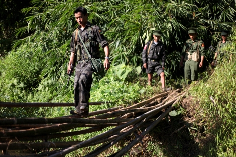 KIA soliders cross broken wood bridge in Lawayang frontline. After Lajayang frontline was fallen to government troops early 2013, Kachin Independence Army – military wing of Kachin Independence Organization- has retreated to Lawayang, where they have reorganized frontline to continue their fight. (Photo © Lee Yu Kyung)