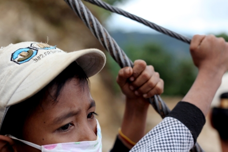 An IDP child firmly holds rope which are attached to the truck for safety purpose as the truck doesn't have enclosing walls. (Photo © Lee Yu Kyung)