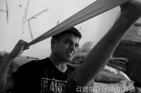 로힝야 보트 난민 무하마드 라피크(18)가 고무줄 등을 이용하여 자가 재활 치료를 하고 있다. 난민 밀항선과 인신매매캠프에서 무릎 굽은 자세를 강요받은 채 여러 달 보낸 보트 난민들은 말레이시아로 풀려난 이후 대부분 마비 증세를 경험하며 걸음을 제대로 걷지 못한다. (Photo © Lee Yu Kyung 2014)