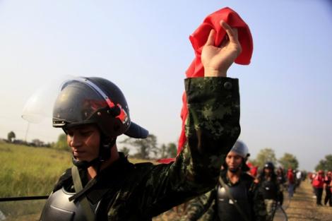 » 2010년 레드셔츠 진압에 나섰다가 시위대와 협상 뒤 현장에서 빠지던 한 병사가 빨간 수건을 들어 보이고 있다. 타이군의 사병 다수가 레드 성향이 강한 빈곤층이거나 동북부 지역 이산 출신이고 이들은 '수박병사'로 불린다. (Photo © Lee Yu Kyung)