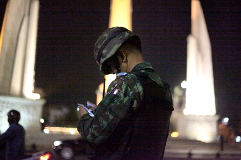 A soldiers near Democracy Monument in Bangkok was checking Social Network System (or SNS) as there's attempt for gathering by handful of activists to support for students, who were arrested days ago for 'three finger salute' at the cinema screening 'Hunger Game'. Three fingers salute has become a symbol of resistance against authoritarian rule in Thailand. And now it's banned. (© Lee Yu Kyung 2014)