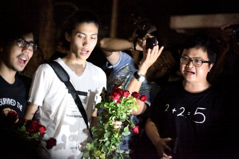Student activists and human rights lawyer together sang a song at a small gathering near Democracy Monument on November 23. Students were among those who were arrested 'three finger salute' at the cinema screening 'Hunger Game' in November. Three fingers salute has become a symbol of resistance against authoritarian rule in Thailand. And now it's banned. (© Lee Yu Kyung 2014)