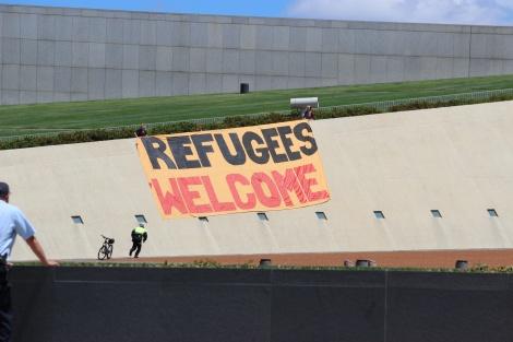 """2013년 호주 수도 캔버라 국회의사당 건물로 잠입한 난민운동가들이  건물 지붕에 """"난민들을 환영한다""""는 플랑카드를 거는 기습 시위를 벌이고 있다. (© Peter Boyle)"""