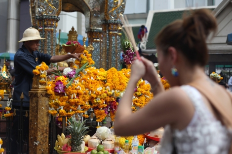 A worker at Erawan Shrine has kept cleaning while prayers have come ongoing. Workers at the Shrine allegedly found remains of victims of the deadly bomb, which killed more than 20. There's criticism towards authority not to have thoroughly checked the scene to collect evidence. (© Lee Yu Kyung)