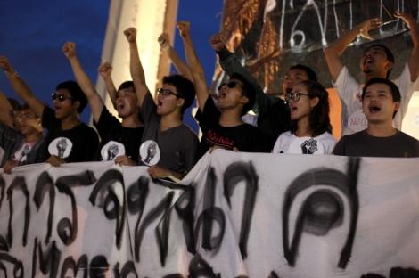 """지난 6월25일 타이 방콕 민주탑에서 """"군정 물러가라""""는 구호를 외친 학생들. 이들은 5명 이상 집회를 금한 군정 명령 3호 위반은 물론 선동죄 혐의로 연행됐다. 현재 방콕 리멘트 감옥과 여성중앙교도소에서 군사재판을 기다리고 있다. (© Lee Yu Kyung 2015)"""