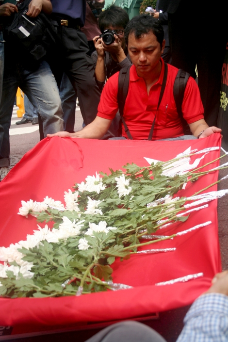 Flag & Flower performance for those who killed in the crackdown on Shaffran Revolution days ago. Nay Tun Naing in Red Shirt / Oct 2 2007, Seoul Korea (© Lee Yu Kyung)
