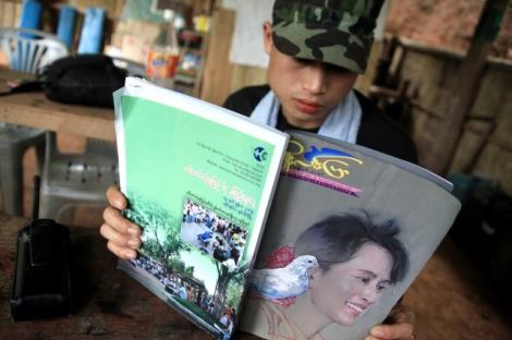 2009년 버마-타이 국경 반군 지역에서 카렌 병사가 아웅산 수치를 표지 모델로 한 시사잡지를 읽고 있다. 군사독재 시절 아웅산 수치는 버만족, 소수민족 할 것 없이 모두의 지지를 받았다. 버마가 개방 노선을 걸어온 지난 4년간 그는 독선적 리더십을 보이며 소수민족 문제에 침묵해왔다. (© Lee Yu Kyung)