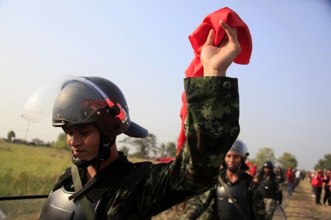 A soldier waving a red scarf as the unit was withdrawing from crowds of Red Shirt protesters in 2010. Thailand is one of more than 30 countries on earth implementing conscription. Many of conscripts are said to be from country's north east where many of Red Shirts are hailed. (© Lee Yu Kyung)