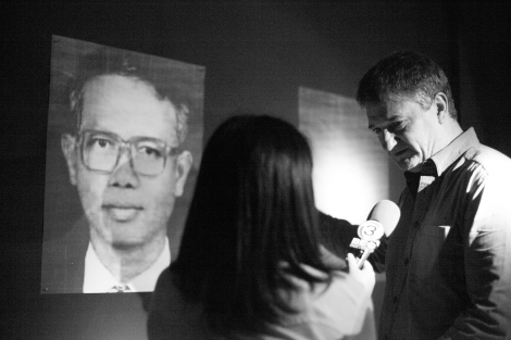 Thai journalist is interviewing foreign audience in front of the portrait of Somchai Neelapaijit (© Lee Yu Kyung)