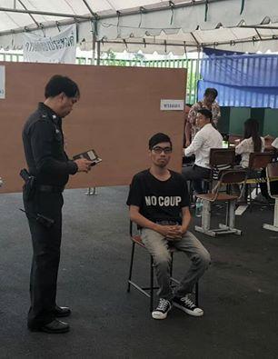 """8월 7일 방콕 남동부 방나 지역 한 투표소에서는 'No Coup'가 적힌 티셔츠를 입고 나타난 유권자 피야랏 총텝씨가 자신의 투표용지를 공개적으로 찢으며 """"독재자는 물러가라. 민주주의 만세""""를 외쳤다. 그의 항의투표 행위 후 경찰이 그의 신분증을 보고 있다. (Source : Facebook)"""